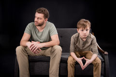 Upset father and son sitting on sofa and looking away. Family problems concept royalty free stock images