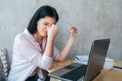 Upset fatigued overworked young business woman taking off glasses tired of computer work, exhausted student suffers from blurry. Vision after long laptop use royalty free stock image