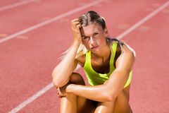 Upset female athlete sitting on running track. On a sunny day Stock Photos