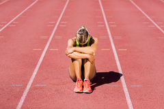 Upset female athlete sitting on running track. On a sunny day Royalty Free Stock Image