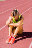 Upset female athlete sitting on running track. On a sunny day Stock Photography