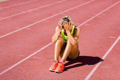 Upset female athlete sitting on running track. On a sunny day Stock Photo