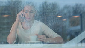 Upset female having angry phone conversation while sitting in a cafe. Viewed through the window. Professional shot on BMCC RAW with high dynamic range. You can stock video