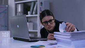 Upset female office employee looking desperately at pile of paper lying on desk. Stock footage stock video