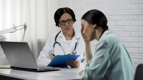 Upset female patient listening to doctor, therapist making prescription, health stock images