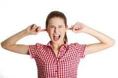 Upset female teen clogging her ears. Front view portrait of a young angry female caucasian teen clogging her ears and shouting, on white Stock Image