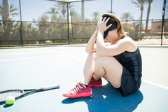 Upset tennis player after losing the match. Upset female tennis player sitting on the court with her hand on head after losing the tennis match outdoor Royalty Free Stock Photos