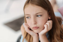 Upset female youngster looking into vacancy. Sad times. Not very happy schoolgirl resting her chin on hands while relaxing on her bed and thinking about Stock Photo