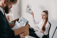 Upset fired businessman with cardboard box and angry businesswoman in office Royalty Free Stock Image