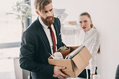 Upset fired businessman with cardboard box and angry businesswoman in office Royalty Free Stock Photos
