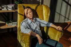 Upset fit man wearing a shirt and blue jeans while sitting in yellow chair. Short-haired man resting. Upset fit man wearing a shirt and blue jeans while sitting stock photography