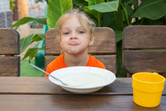 Upset five year old girl poses faces unwilling to eat porridge for breakfast. Five-year girl sits at a table with a sour face and did not want to eat porridge Royalty Free Stock Photos