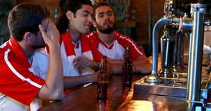 Upset friends interacting while having beer at bar counter stock footage