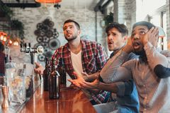 Upset friends watching football and drinking beer royalty free stock images