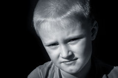 Upset frightened child (boy). Upset abused frightened little child (boy), close up horizontal dark portrait with copy space royalty free stock photos