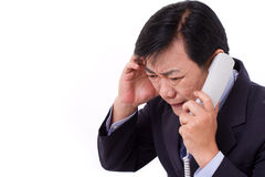 Upset, frustrated manager receiving bad news via telephone call. White isolated Royalty Free Stock Image