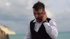 Portrait of an upset, frustrated man talking on a mobile phone near the sea with a stunning view. Businessman talking by. Upset frustrated young man talking by stock video
