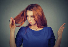 Upset frustrated young woman surprised she is losing hair, noticed split ends Stock Photos