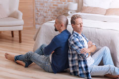 Upset gay couple sitting with crossed arms Royalty Free Stock Image