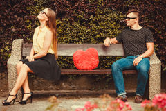 Upset girl on bench with boy. Love romance valentines dating concept. Upset girl on bench with boy. Angry young women turns her back on boyfriend Stock Photo