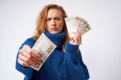 A frustrated girl in a sweater holding money, on a gray background. An upset girl in a blue sweater gives a piece of hryvnia money, on a gray background royalty free stock photography