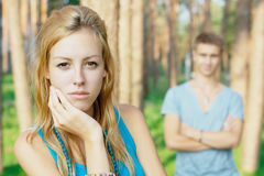 Upset girl with a boy at the background Royalty Free Stock Photo