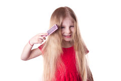 Upset girl combing tangled blonde long hair Royalty Free Stock Images