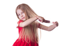 Upset girl combing tangled long hair Royalty Free Stock Images
