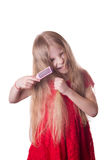 Upset girl combing tangled long hair Royalty Free Stock Photography