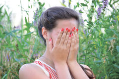 Upset girl covers her face with hands. Upset woman covers her face with hands stock image