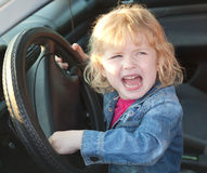 Upset girl crying in the car, in soft focus Stock Photos