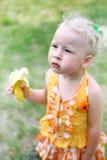 Upset the girl eats a banana Royalty Free Stock Photo