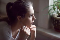 Upset girl feel down having relationships problems. Upset young woman look far in window thinking about personal troubles, sad female feeling blue after breakup royalty free stock photos