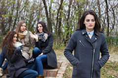 Upset girl with friends gossiping Stock Photo