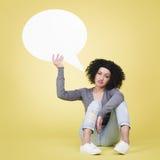 Upset girl holding a white speech balloon with copyspace. Stock Photos