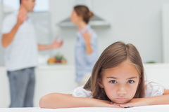 Upset girl listening to parents quarreling. In the kitchen Royalty Free Stock Photography