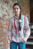 Upset girl near brick wall. Sad teenage girl with a pigtail near red brick wall Royalty Free Stock Photo