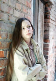 Upset girl near brick wall. Upset teenage girl with long hair near brick wall Royalty Free Stock Images