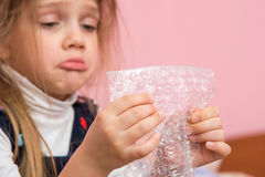 Upset girl pouting cheeks eats bubbles packaging film Royalty Free Stock Photography