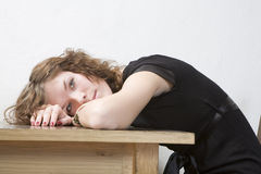 Upset girl put her head down table. Royalty Free Stock Photos