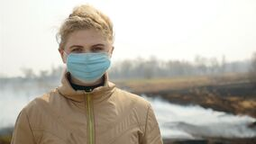 Upset girl puts on a medical mask. Smoking field. Burnt grass around. Environmental pollution. Slow motion. Close-up