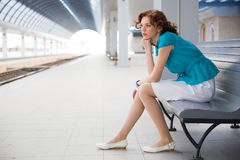 Upset girl on railway station Stock Photos