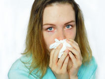 An upset girl with runny nose. Is hiding her nose behind the handkerchief Royalty Free Stock Photos