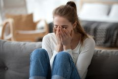 Upset girl sit on sofa crying after breakup. Upset young female sit on couch at home crying over ended relationships, unhappy girl cover face feeling down after royalty free stock photo