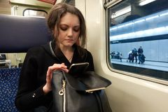 The upset girl sits in the subway car and reads the bad news on the smartphone online Royalty Free Stock Image
