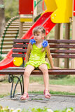 Upset girl sitting on bench on the background of the playground Royalty Free Stock Photography
