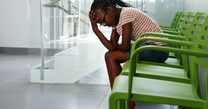 Upset girl sitting on chair in corridor. At hospital stock video footage