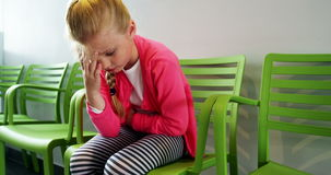 Upset girl sitting on chair in hospital corridor. Upset girl sitting on chair in corridor at hospital stock footage