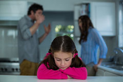 Upset girl sitting while couple having argument in background Stock Photo