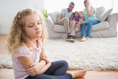 Upset girl sitting on floor while parents enjoying with brother Stock Images